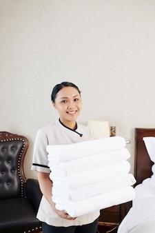 Empregada com toalhas no hotel