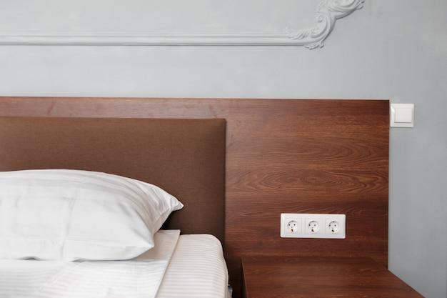 Empregada de cama com travesseiros brancos limpos e lençóis na sala de beleza.
