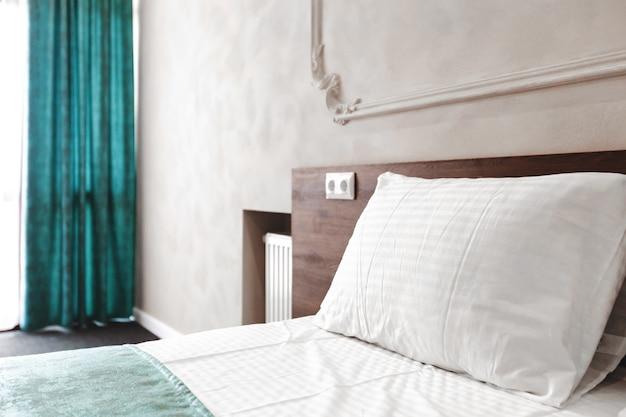 Empregada de cama com travesseiros e lençóis brancos limpos