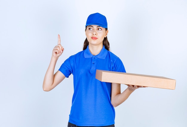 Empregada de entrega de mulher com caixa de papel ofício apontando para cima.