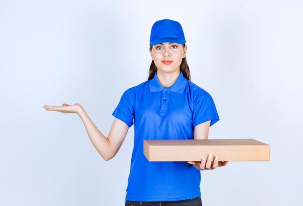 Empregada de entrega de mulher de uniforme, segurando a caixa de papel ofício.