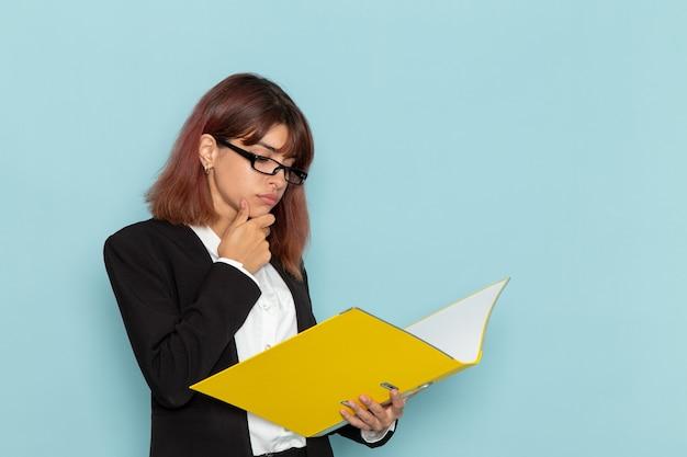 Empregada de escritório em terno estrito lendo documento na superfície azul de vista frontal