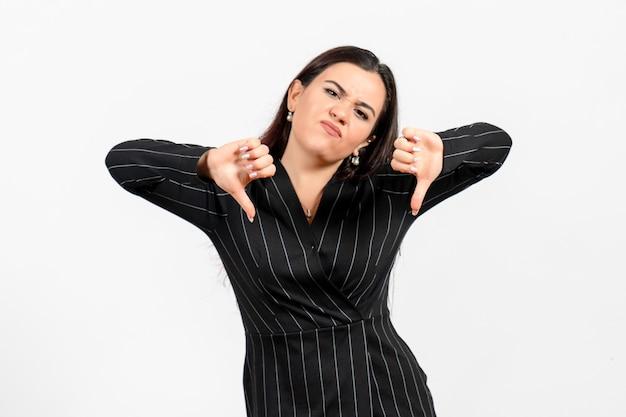 Empregada de escritório em terno preto estrito mostrando sinal diferente em branco