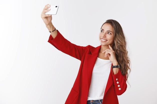 Empregada de escritório encantadora e moderna tirando selfie, postando em blog on-line, contando aos seguidores um novo emprego, estendendo a mão segurando um smartphone e se fotografando sorrindo na tela