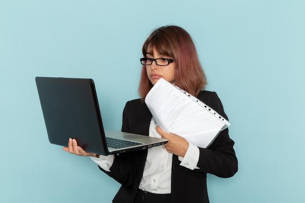 Empregada de escritório feminina de terno rígido, vista frontal, segurando documentos e laptop na superfície azul