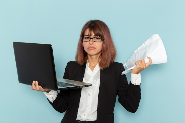 Empregada de escritório feminina de terno rígido, vista frontal, segurando papéis e laptop na superfície azul