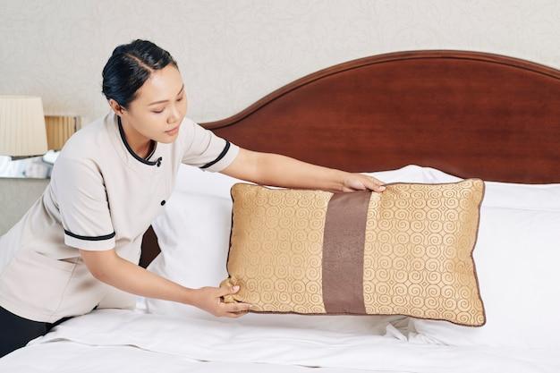 Empregada de hotel decorando a cama com almofadas ao preparar o quarto para o próximo hóspede