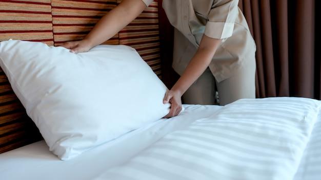 Empregada de hotel fazendo a cama em hotel de luxo