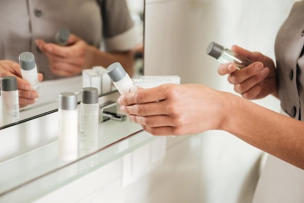 Empregada de hotel jovem colocando acessórios de banho em uma casa de banho