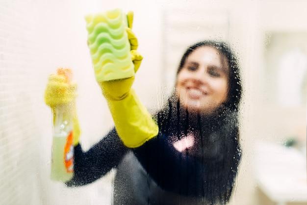 Empregada de luvas limpa vidros com spray de limpeza, interior de banheiro de hotel