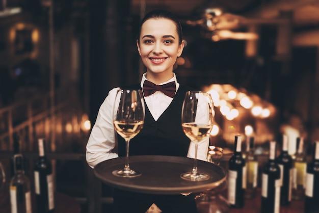 Empregada de mesa alegre que guarda a bandeja com vidros do vinho branco.