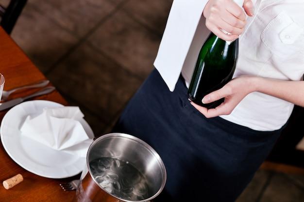 Empregada de mesa com champanhe no restaurante