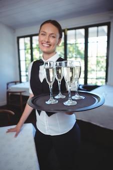 Empregada de mesa com uma bandeja de flauta de champanhe