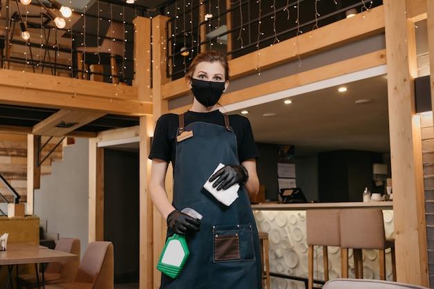 Empregada de mesa em luvas médicas descartáveis pretas usa uma máscara facial médica