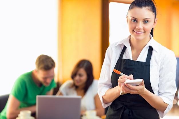 Empregada de mesa escrevendo um pedido com alunos usando laptop na cafeteria
