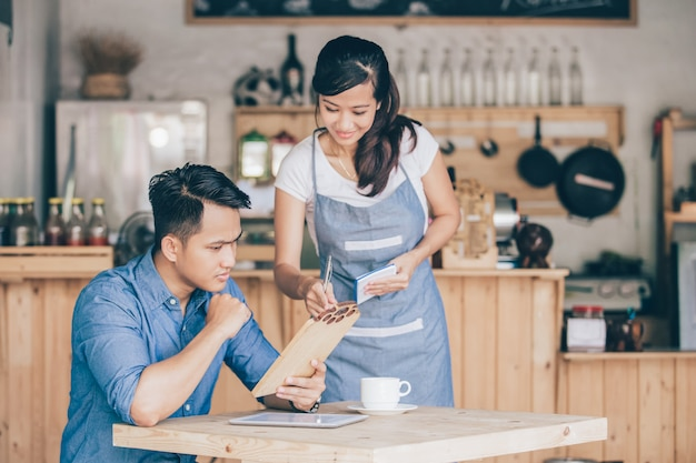 Empregada de mesa feminina explicar sobre o menu para seu cliente
