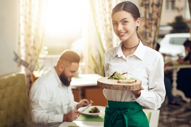 Empregada de mesa jovem retrato segurando o sanduíche no prato