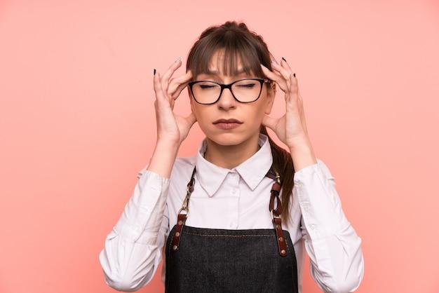 Empregada de mesa nova sobre cor-de-rosa infeliz e frustrado com algo. expressão facial negativa