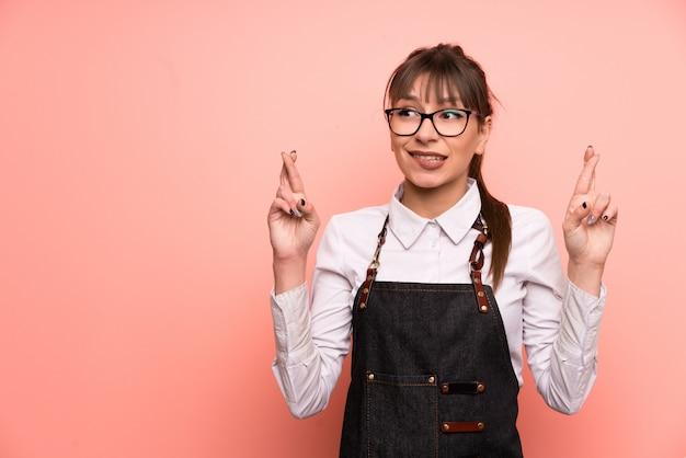 Empregada de mesa nova sobre o fundo cor-de-rosa com cruzamento dos dedos