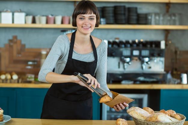 Empregada de mesa sorridente croissants em saco de papel no café
