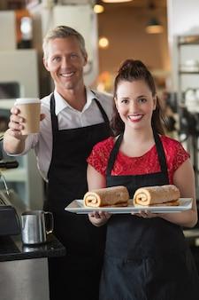 Empregada de mesa sorrindo para a câmera mostrando bolos