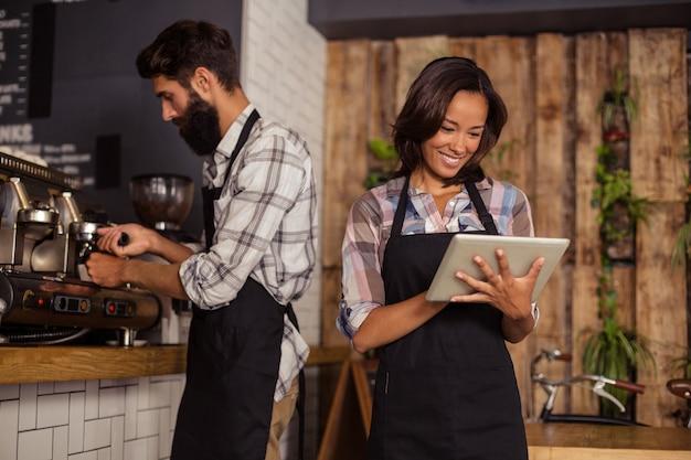 Empregada de mesa usando tablet digital enquanto garçom preparando café no fundo