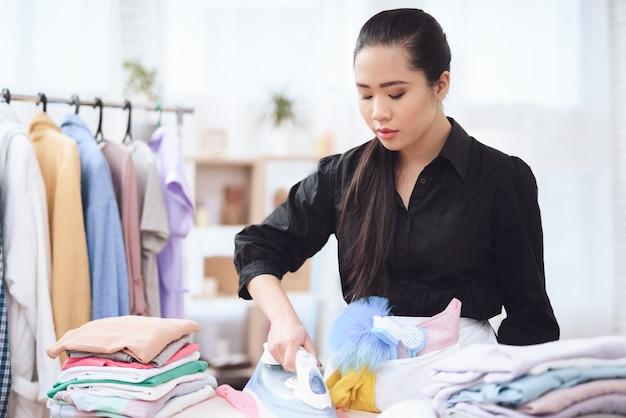 Empregada de passar roupas cuidadosamente com serviço de hotel
