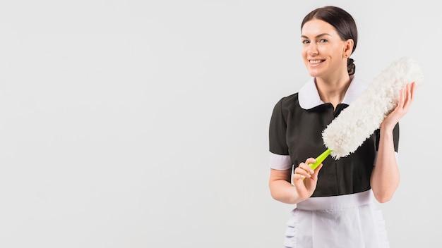 Empregada de uniforme, sorrindo com espanador