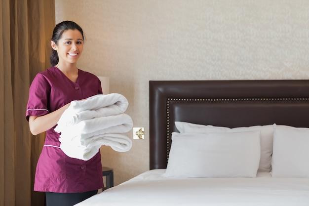 Empregada do hotel que segura pilha de toalhas limpas