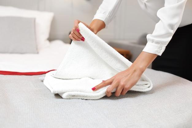 Empregada dobrando toalhas limpas no quarto do hotel