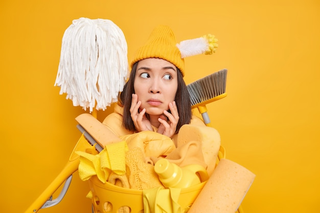 Empregada doméstica asiática mantém as mãos no rosto olhando para longe e usa diferentes ferramentas de limpeza para colocar as poses em ordem perto do cesto de roupa suja em amarelo vivo