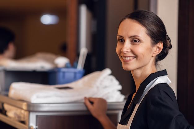 Empregada doméstica com um carrinho de limpeza e material de limpeza