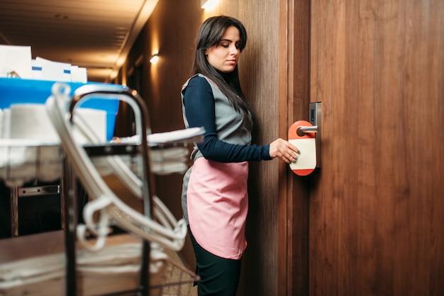 Empregada doméstica de uniforme terminou de limpar o quarto