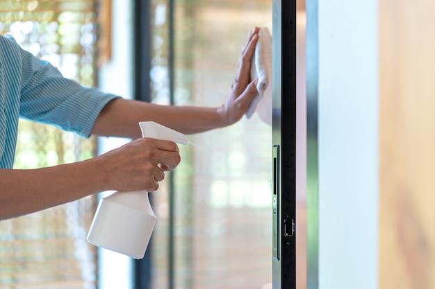 Empregada doméstica está limpando a porta do espelho na frente da sala de reuniões