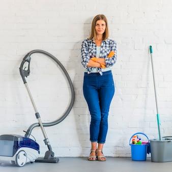 Empregada doméstica fêmea bonita com a mão dobrada que está perto dos equipamentos da limpeza