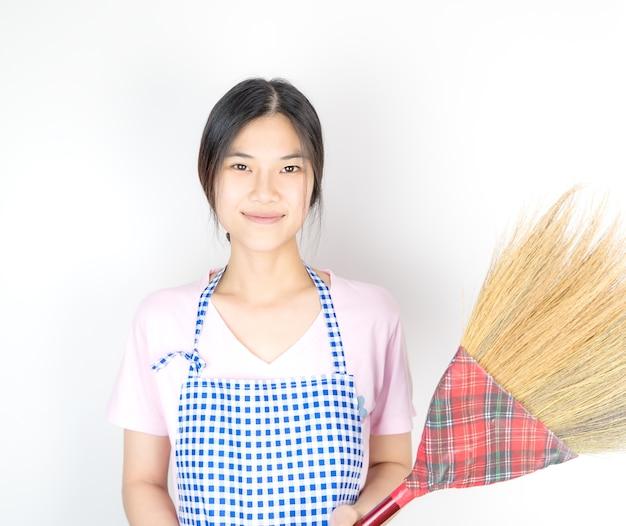 Empregada doméstica houswife asiática está segurando a vassoura para limpeza