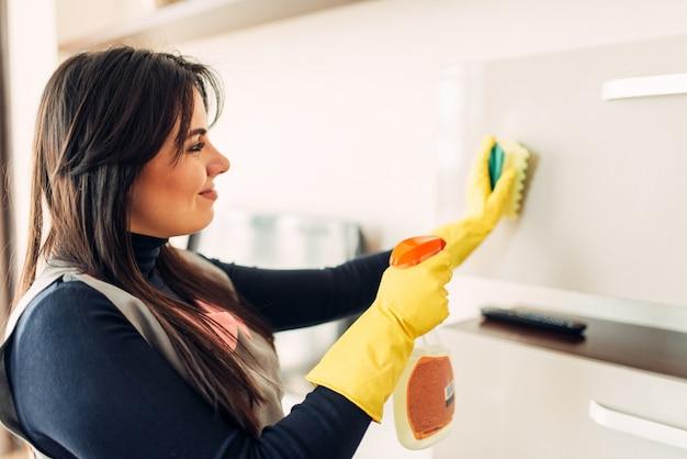 Empregada doméstica limpa móveis com spray de limpeza