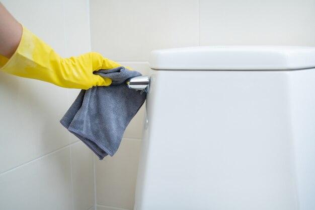 Empregada doméstica limpando o autoclismo usando álcool e solução de limpeza líquida. conceito de proteção covid-19, sempre limpando equipamentos no dia a dia. saneamento e saúde.
