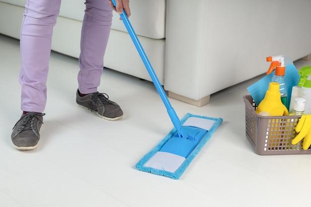 Empregada doméstica limpando o chão na sala, close-up mulher fazendo tarefas domésticas