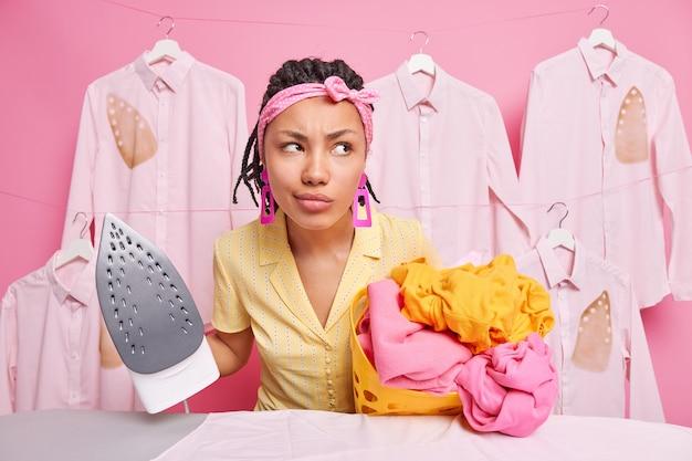 Empregada doméstica pensativa de pele escura descontente olha pensativamente para longe segura pilha de roupas desdobradas e ferro elétrico a vapor indo para acariciar linho usa bandana vestido casual funciona na lavanderia