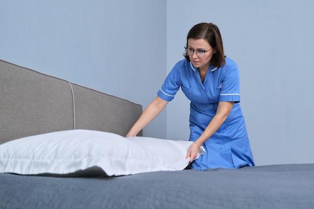 Empregada doméstica profissional de meia-idade preparando o quarto de hóspedes fazendo a cama