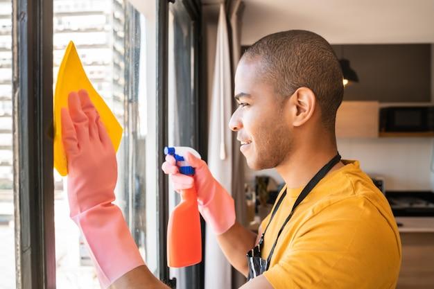 Empregada doméstica que limpa a janela de vidro em casa.