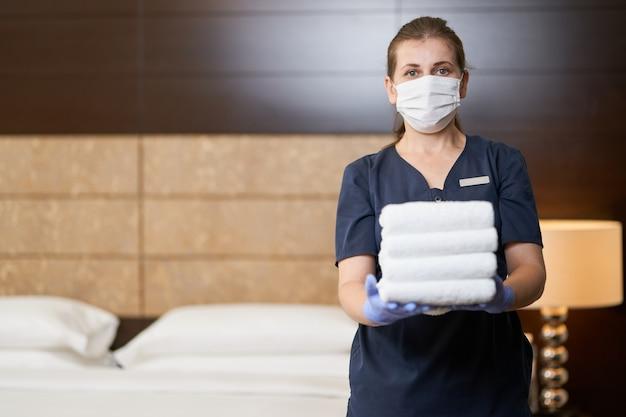 Empregada doméstica segurando toalhas limpas dobradas no quarto