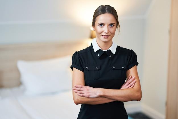 Empregada em pé no quarto do hotel