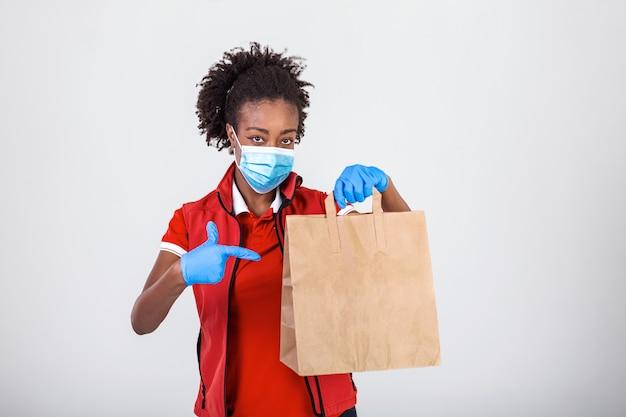 Empregada entregadora com uma luva máscara de uniforme de camiseta vermelha segurando um pacote de papel artesanal com comida