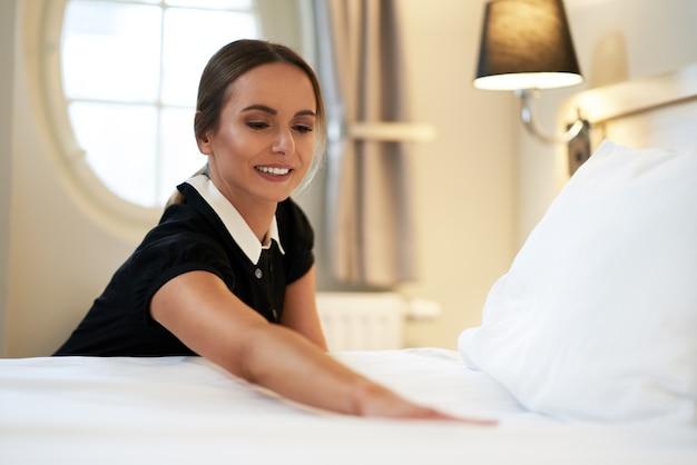 Empregada fazendo cama em quarto de hotel