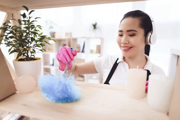 Empregada filipina limpando com espanador de penas.