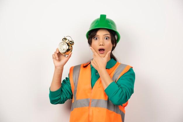 Empregada imaginando com capacete e segurando um relógio.