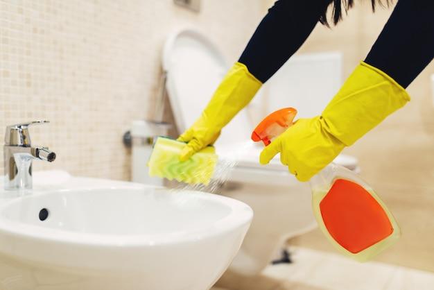 Empregada limpa o bidê com spray de limpeza