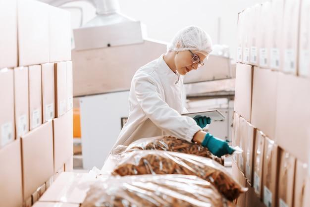 Empregada loira caucasiana em uniforme estéril em pé e lidar com logística de produtos. interior da fábrica de alimentos. tablet na mão.